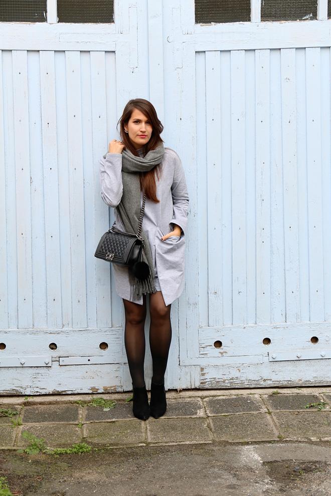 Outfit graues Kleid vor hellblauem Tor